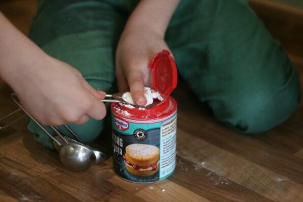 child measuring a tsp of baking powder