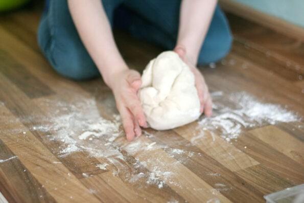 child kneading bagel dough
