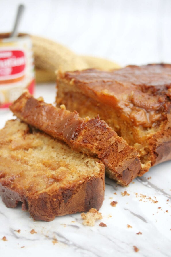 Caramel banana bread sliced on a serving plate with a tin of caramel and bananas in the background