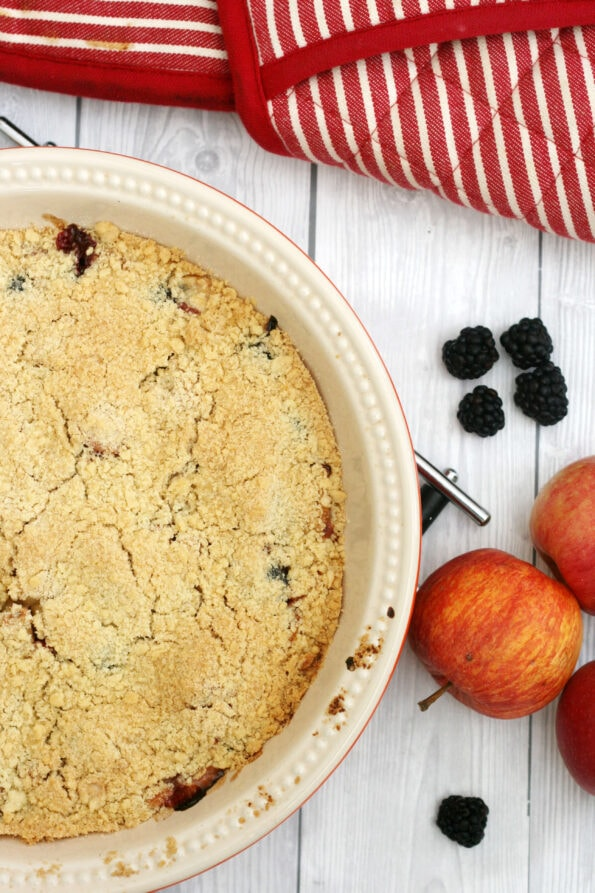 Apple and blackberry crumble in a pie dish with fruit next to it