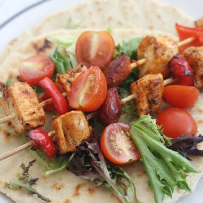 chicken and chorizo skewers on a flatbread with salad