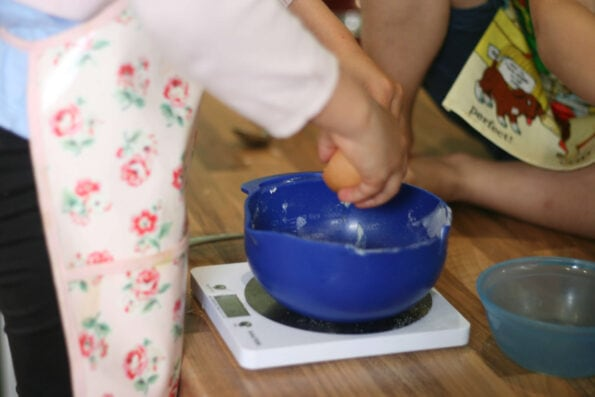 child cracking an egg into a bowl