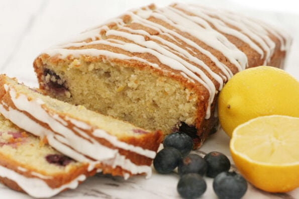 Lemon and blueberry loaf with 2 slices and blueberries and a cut lemon at the side