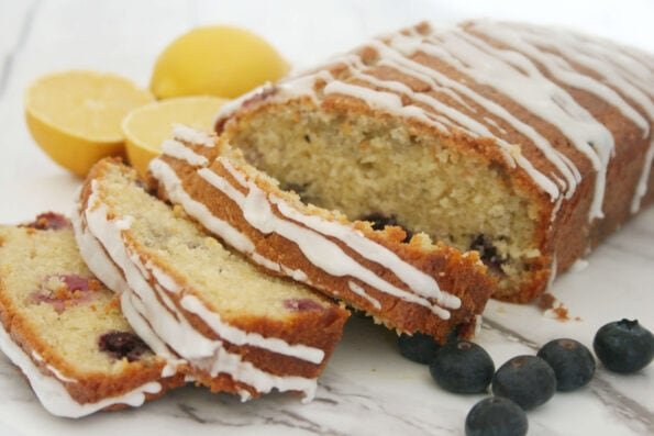 lemon blueberry loaf on a serving plate with lemons and blueberries on the side