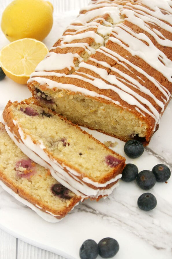 Lemon and blueberry loaf sliced, with a cut lemon and blueberries on the side