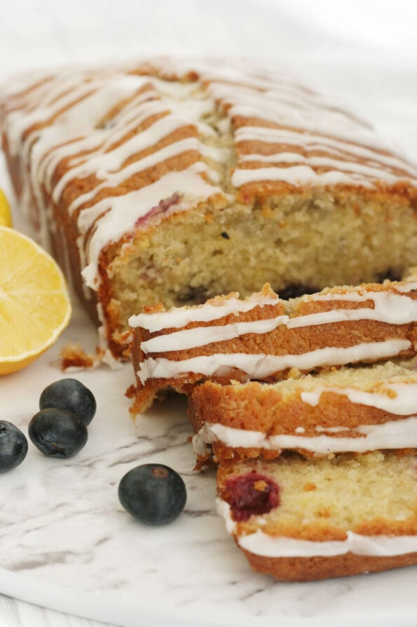 Lemon and blueberry loaf sliced with a cut lemon and blueberries at the side