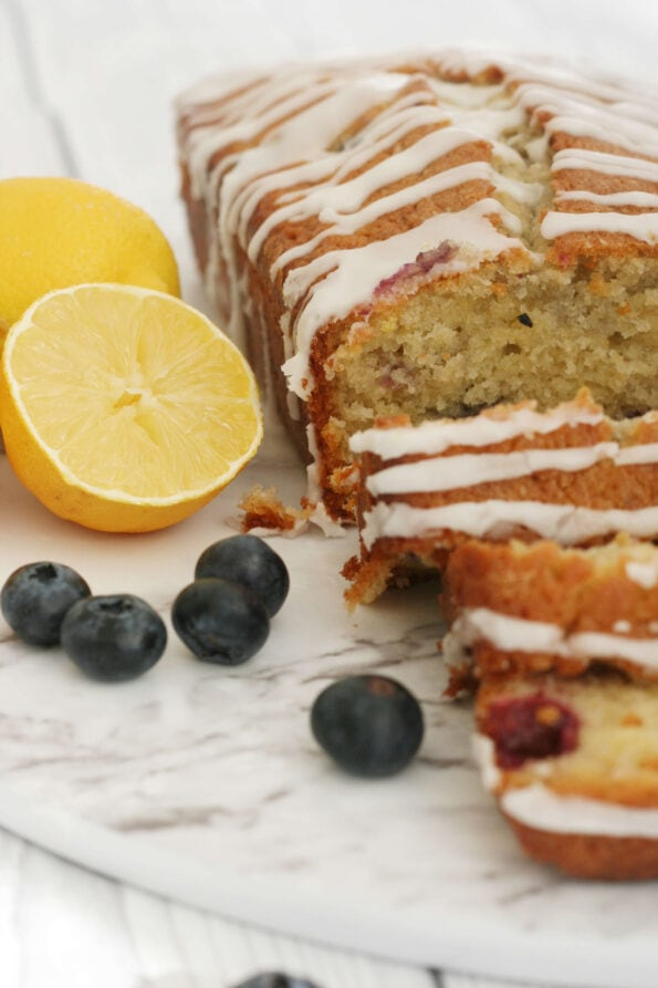 Lemon blueberry loaf sliced with a cut lemon and blueberries on the side