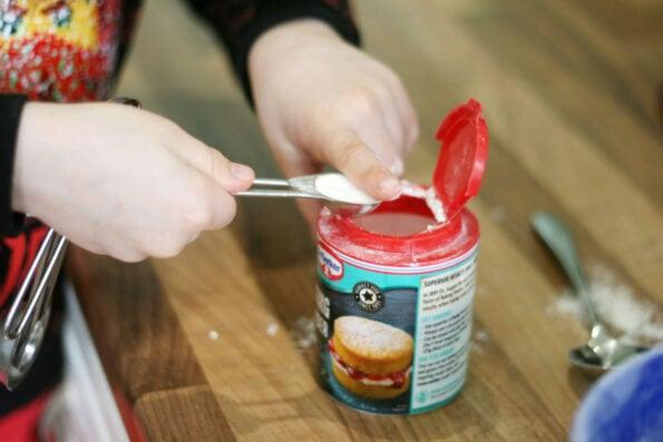 child measuring baking powder