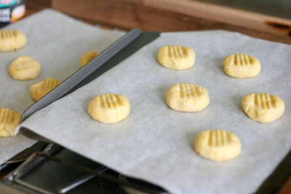 orange biscuits on a baking tray before going in the oven