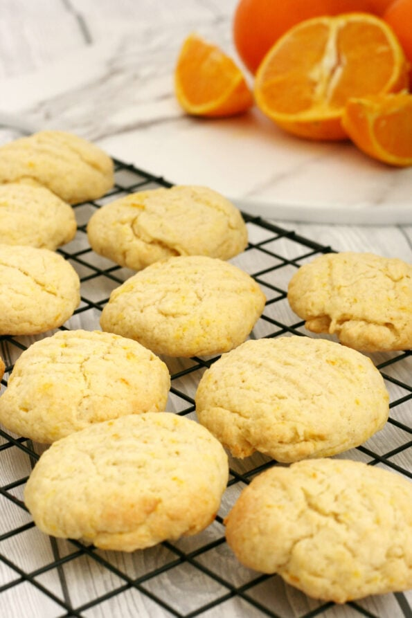 Orange biscuits on a wire rack with oranges in the background