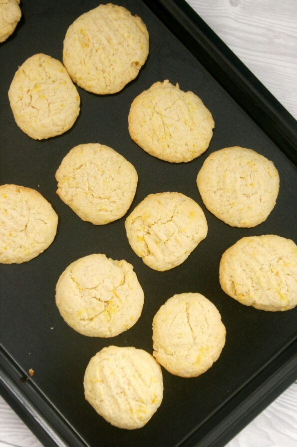 Orange biscuits on a black baking tray