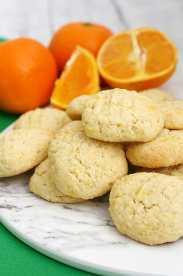 Orange biscuits in a pile with oranges arranged in the background.