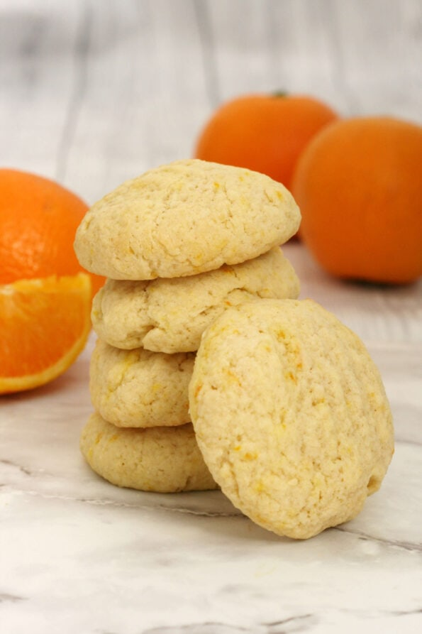 Orange biscuits arranged in a stack with oranges in the background