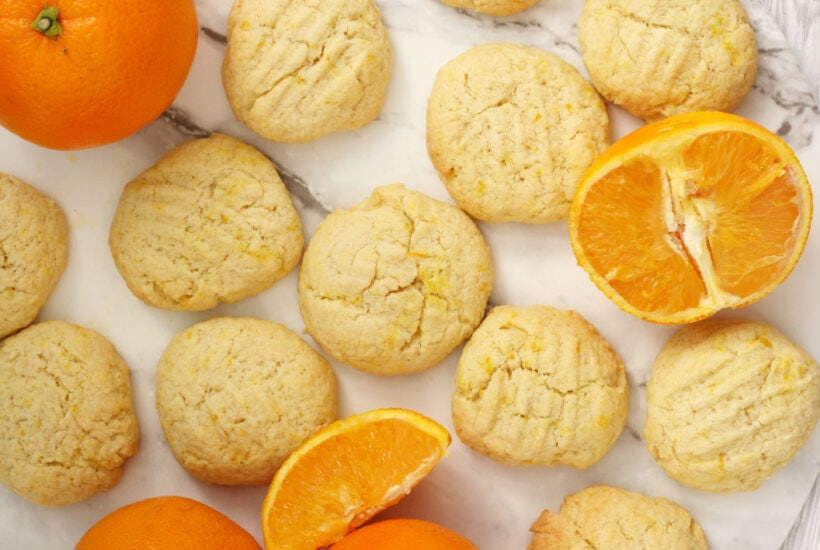 orange biscuits arranged on a serving plate with some orange segments