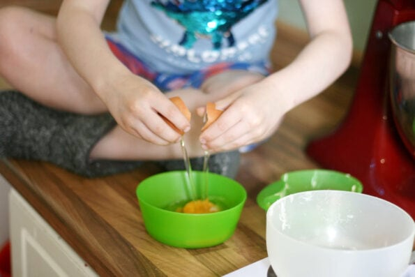 child cracking an egg into a green bowl