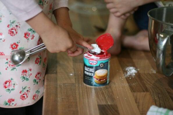child measuring a teaspoon of baking powder
