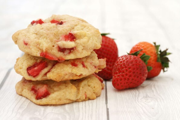 Strawberry cookies in a pile with 3 strawberries on the side
