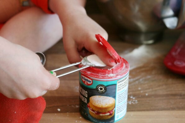 child measuring baking powder