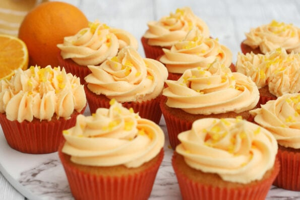 orange cupcakes with an orange in the background