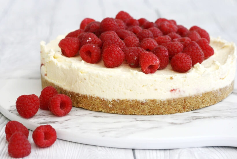 White chocolate cheesecake with raspberries on top and a few on the side