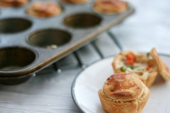 mini chicken pot pie on a plate next to more in a muffin tin