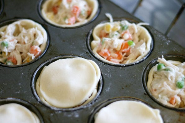 mini pot pies being filled in a muffin tin