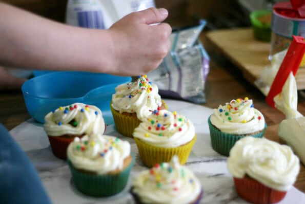 child adding sprinkles to a funfetti cupcakes