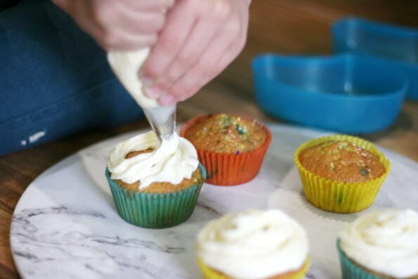 child piping buttercream on to funfetti cupcakes