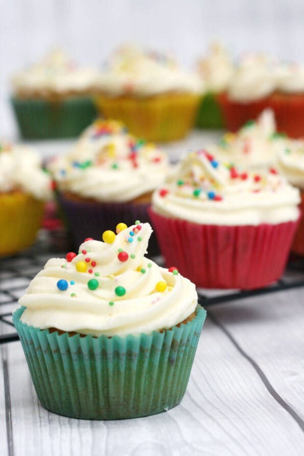 Funfetti cupcakes in colourful cases on a wire rack