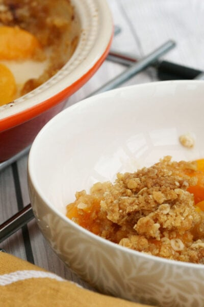 peach crumble in a bowl with a dish behind