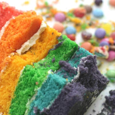 rainbow cake slice surrounded by colourful sweets