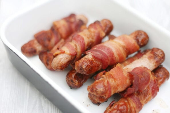 Pigs in blankets (sausages wrapped in bacon) on a white serving plate