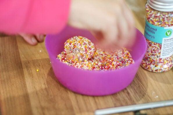 rolling cookie dough in sprinkles