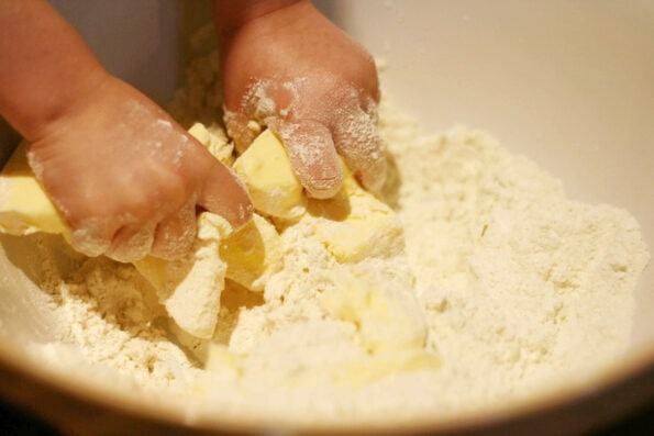 child rubbing in butter to flour