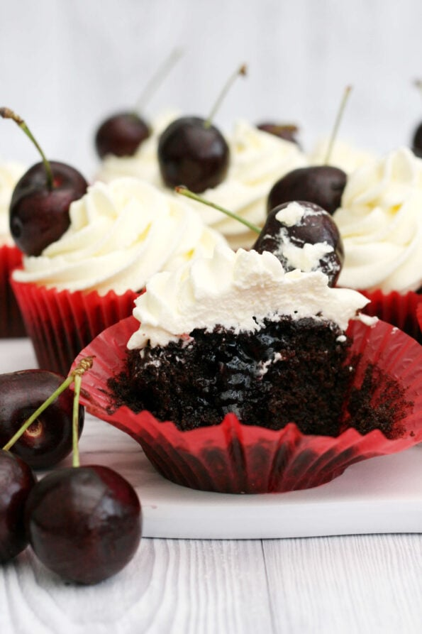 Black forest cupcake cut down the middle with cherries on the side