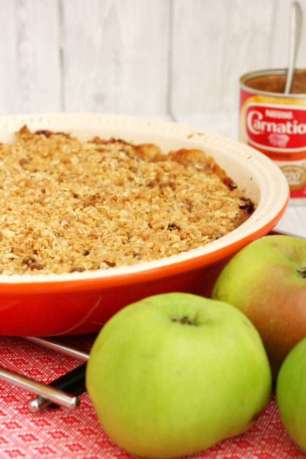 caramel apple crumble in a dish with apples at the side.