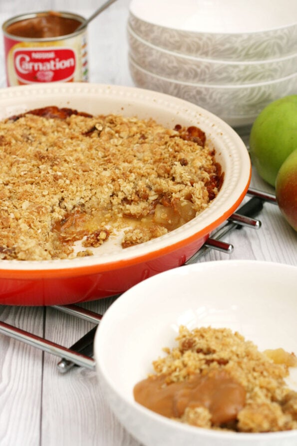 caramel apple crumble in a dish with some bowls at the side