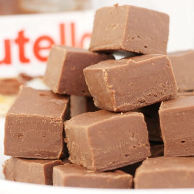 Nutella fudge in a pile with a jar of Nutella in the background